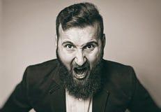 衣服的有胡子的人在愤怒状态呼喊  免版税库存图片