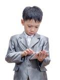 衣服的男孩使用片剂计算机 免版税库存照片