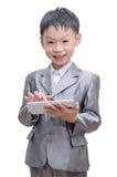 衣服的男孩使用片剂计算机 库存图片
