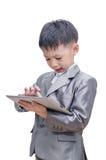 衣服的男孩使用片剂计算机 免版税图库摄影