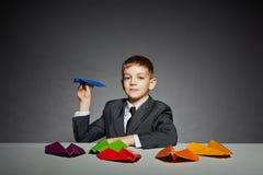 衣服的男孩发射蓝纸飞机的 库存照片
