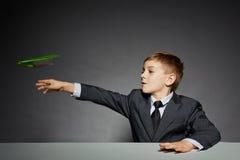 衣服的男孩发射绿皮书飞机的 库存图片
