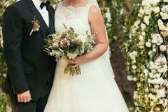 黑衣服的白色婚礼礼服的新郎和新娘与土气 免版税图库摄影