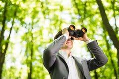 衣服的确信的英俊的商人与看在他的市场上的双筒望远镜竞争者在绿色公园 到达天空的企业概念金黄回归键所有权 免版税图库摄影