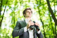 衣服的确信的英俊的商人与看在他的市场上的双筒望远镜竞争者在绿色公园 到达天空的企业概念金黄回归键所有权 免版税库存照片