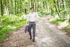 衣服的英俊的确信的商人走在绿色公园的 到达天空的企业概念金黄回归键所有权 免版税库存图片