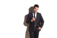 衣服的英俊的站立对墙壁的人和领带 免版税库存照片