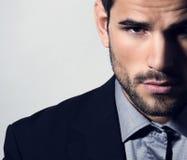 衣服的英俊的年轻人在灰色背景 库存图片