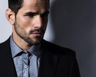衣服的英俊的年轻人在灰色背景 免版税库存图片