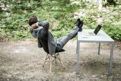 衣服的轻松的商人与在办公桌上的头天花板和腿在成功的工作以后在绿色公园 自由职业者放松af 免版税库存图片