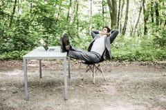 衣服的轻松的商人与在办公桌上的头天花板和腿在成功的工作以后在绿色公园 自由职业者放松af 库存图片