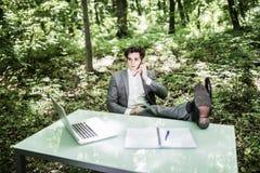 衣服的轻松的商人在办公桌谈话的绿色公园在被做的手机成功的工作 到达天空的企业概念金黄回归键所有权 图库摄影
