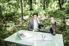 衣服的轻松的商人在办公桌谈话的绿色公园在被做的手机成功的工作 到达天空的企业概念金黄回归键所有权 免版税库存照片