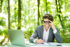 衣服的运作在膝上型计算机在办公室桌上认为在绿色森林公园的年轻英俊的商人画象  到达天空的企业概念金黄回归键所有权 库存照片