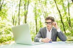 衣服的运作在膝上型计算机在办公室桌上认为在绿色森林公园的年轻英俊的商人画象  到达天空的企业概念金黄回归键所有权 免版税库存图片