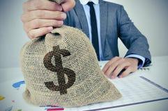 衣服的年轻人与与美元信号的一个粗麻布金钱袋子 免版税库存照片