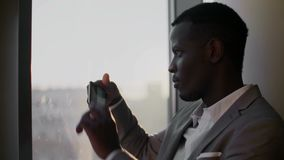 衣服的年轻黑人使用智能手机支持的窗口在少数民族居住区办公室在阳光下 股票视频