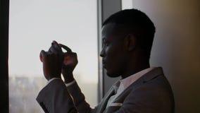 衣服的年轻黑人使用智能手机支持的窗口在少数民族居住区办公室在阳光下 影视素材
