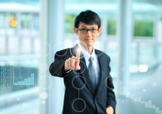 衣服的年轻商人指向以他的手指的接触s 免版税库存图片
