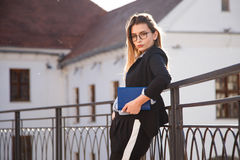 衣服的年轻成功的自由职业者的女孩,与站立的笔记本的玻璃室外 图库摄影