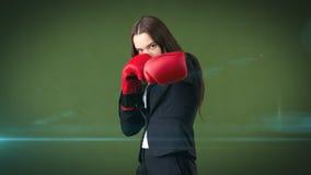 黑衣服的年轻美丽的妇女和站立在作战的白色衬衣摆在与红色拳击手套 到达天空的企业概念金黄回归键所有权 免版税图库摄影