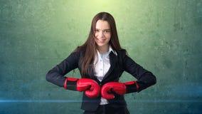 黑衣服的年轻美丽的妇女和站立在作战的白色衬衣摆在与红色拳击手套 到达天空的企业概念金黄回归键所有权 免版税库存照片