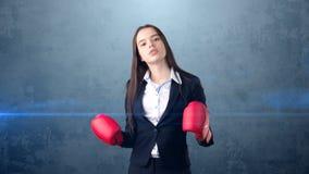 黑衣服的年轻美丽的妇女和站立在作战的白色衬衣摆在与红色拳击手套 到达天空的企业概念金黄回归键所有权 免版税库存图片