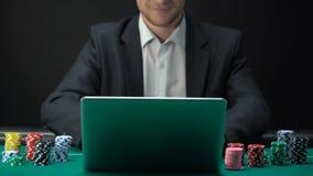 衣服赌博的人在网上在膝上型计算机,拿着赌博娱乐场芯片手中,打赌 股票录像