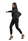 衣服赛跑的年轻可爱的女实业家,当检查在她的手表时的时间 免版税库存图片