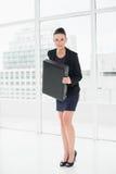 衣服运载的公文包的典雅的女实业家在办公室 免版税库存图片