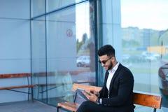 衣服阿拉伯语的人在事务附近投入有片剂的太阳镜 免版税图库摄影