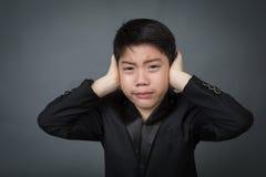 黑衣服翻倒的小亚裔男孩,消沉面孔 库存图片