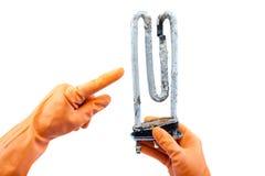洗衣机的损坏的发热设备在手中有rubb的 免版税库存照片