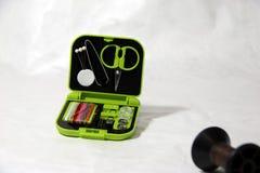 衣物修理集合,剪刀钳子别针穿线针按钮和别针在绿色小接线盒 图库摄影