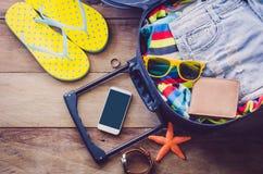 衣物旅客` s护照,钱包,玻璃,手表,巧妙的电话设备,在准备好的行李的一个木地板上旅行 免版税图库摄影