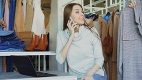 衣物精品店女性所有者在手机在膝上型计算机谈话并且键入 她的助理接近她,和 股票视频