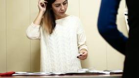 衣物设计师与在演播室桌上的测量一起使用 股票录像