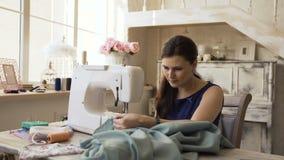 年轻衣物设计师和裁缝妇女与缝纫机一起使用在裁缝演播室 股票录像