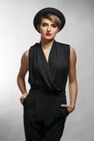戴黑衣裳和一个时兴的帽子的典雅的bussinesswoman画象 免版税库存照片
