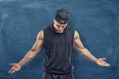 黑衣裳和盖帽的肌肉人有他的头的在蓝色黑板背景降下了 免版税库存照片
