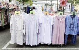 衣裳在与女睡袍一个大样品的一个街市上站立  免版税库存照片