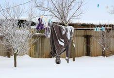 衣裳在农村冬天背景的一条绳索烘干了 库存照片