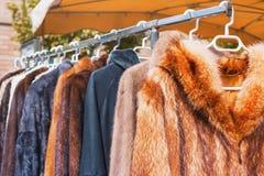 衣裳待售为冬天晒干垂悬在机架在室外跳蚤市场上 免版税库存照片