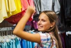 衣裳的十几岁的女孩购物在服装店里面 免版税库存照片