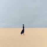 黑衣裳的时髦的女孩走在沙漠的 免版税库存照片