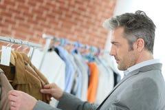 衣裳的英俊的中年人购物 库存照片