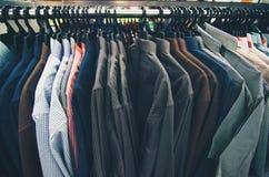 衣裳的选择垂悬在挂衣架的人的在商店销售概念的购物中心 免版税库存照片