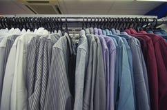 衣裳的选择垂悬在挂衣架的人的在商店销售概念的购物中心 图库摄影