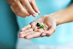 补充维生素 拿着五颜六色的药片的女性手 库存照片