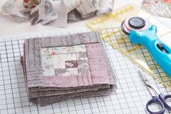 补缀品在工艺席子,堆的原木小屋块块,白色木表面上的缝合的辅助部件 库存图片